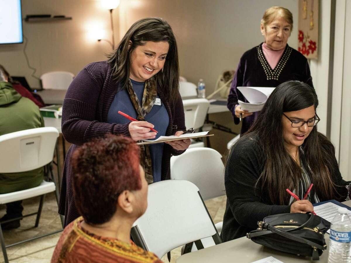 Program Coordinator Summer Wilmoth, center, checks in with congregants of St. John Berchmans Catholic Church on Monday as they begin a program with a faith-based curriculum that works to prevent diabetes and cancer through health lessons and Scripture. Some 35 churches have adopted it.