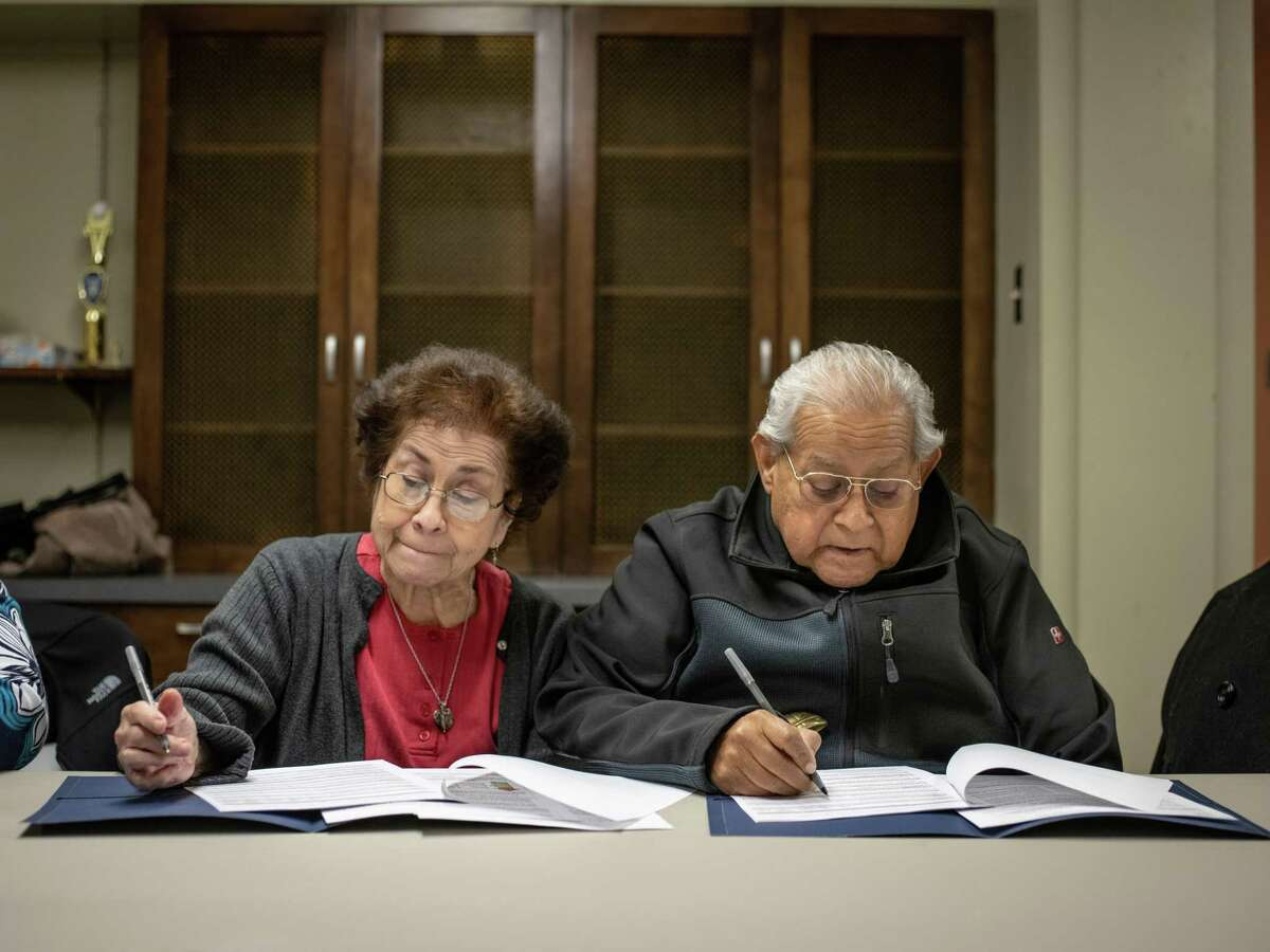 Program participants Lucy and Robert Sanchez answer health questions together Monday for their paperwork as congregants of St. John Berchmans Catholic Church for a program that works to prevent diabetes and cancer through health lessons and Scripture.Some 35 churches have adopted it.