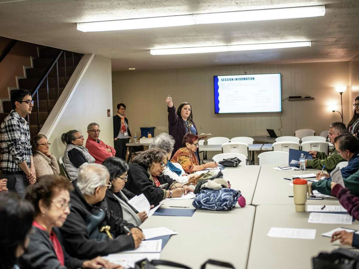 Program Coordinator Summer Wilmoth, center, directs congregants of St. John Berchmans Catholic Church on Monday as they begin a program with a faith-based curriculum that works to prevent diabetes and cancer through health lessons and Scripture. Some 35 churches have adopted it.